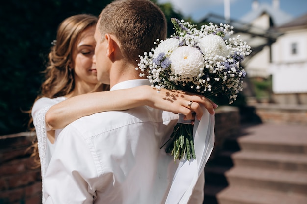 花嫁と新郎は、お互いの手を優しい町の周りを歩く入札を保持 無料写真