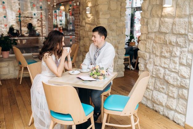 素敵な若い結婚式のカップルは居心地の良いカフェの夕食のテーブルに座っている 無料写真