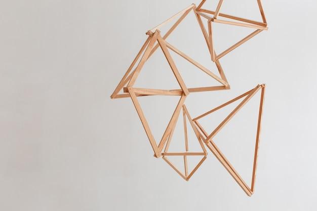 白い壁の背景に隔離された天井から垂れた木製の幾何学的な装飾。 無料写真