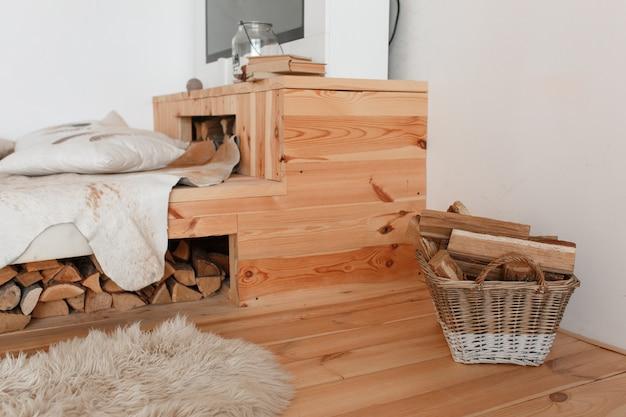 木製のベッドとその下の薪、暖炉のバスケット 無料写真