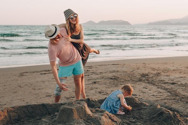 Счастливый молодая семья с маленький ребенок, с удовольствием на пляже. радостная семья. Бесплатные Фотографии
