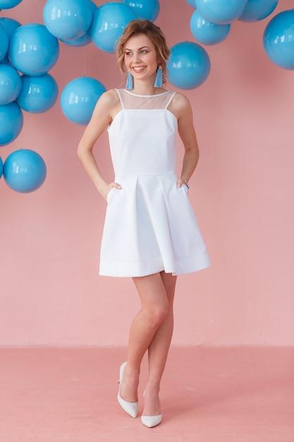 ピンクの壁の背景にポーズを取る白いカクテルドレスの若い女性 無料写真