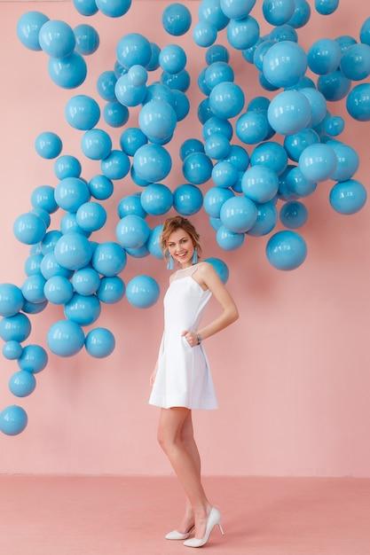 白いカクテルドレスで青い泡のピンクの壁の背景にポーズを取る若い女性 無料写真