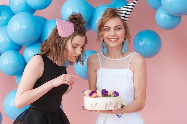 ケーキを持っているパーティーの帽子で二十代の女の子。ピンクの背景と青い風船で分離 無料写真