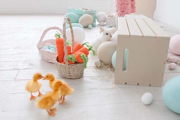 イースター装飾のスタジオルームには、アヒル、ニンジン、塗装された大きな卵が飾られています。 無料写真