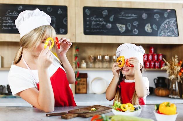 ママと娘は夕食のためにさまざまな野菜を料理するキッチンで楽しい 無料写真