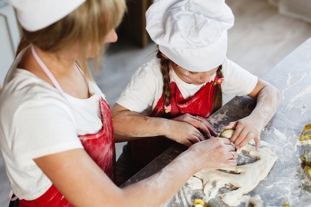 Мама и дочь развлекаются приготовлением печенья с молоком на обеденном столе в уютной кухне Бесплатные Фотографии