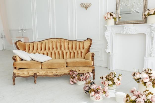 Красивая гостиная в провансе с винтажным коричневым диваном возле камина с цветами и свечами Бесплатные Фотографии