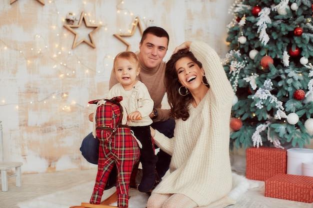 冬の休日の装飾暖色系です。家族写真。ママ、パパとその幼い娘 無料写真