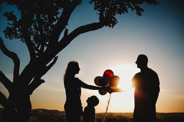 幸せな両親は木の下の緑の芝生の上で子供たちと楽しんでいます 無料写真