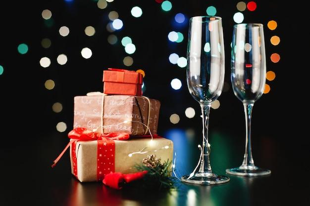 新年とクリスマスの装飾。シャンパンフルート、小さなプレゼントと緑の枝 無料写真