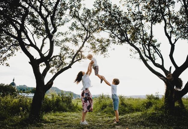 魅力的な若い母親抱擁彼女の幼い息子たちの下に立って入札 無料写真