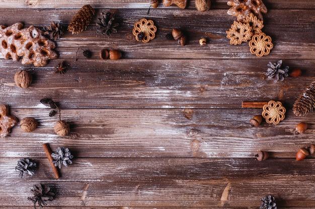 クリスマスの装飾とテキストのための場所。クッキー、シナモンの枝そして円錐形が輪を作る 無料写真