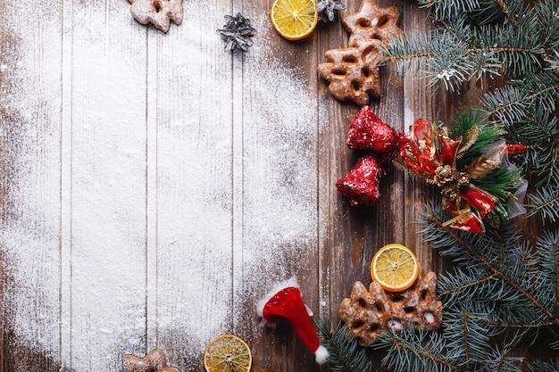 クリスマスの装飾とテキストのための場所。白い雪がクッキーに囲まれたテーブルの上にあります。 無料写真