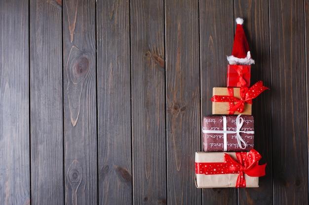 クリスマスの装飾とテキストのための場所。プレゼントで作られた新年の木は木製のテーブルの上にあります。 無料写真