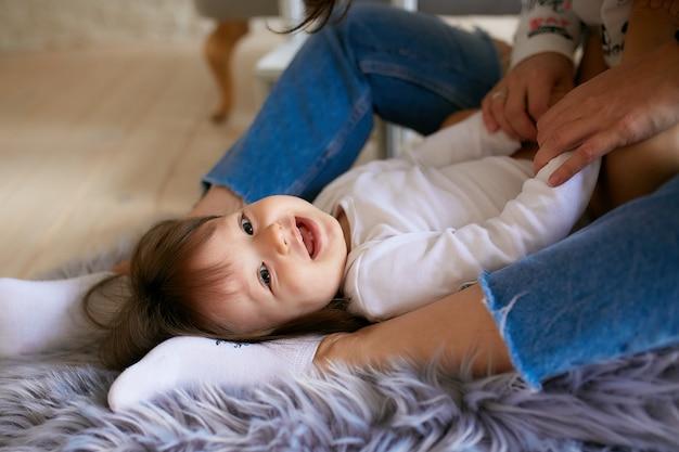 カジュアルなスタイルに身を包んだ小さな女の子と彼女のお母さんは床で遊んで楽しんで 無料写真