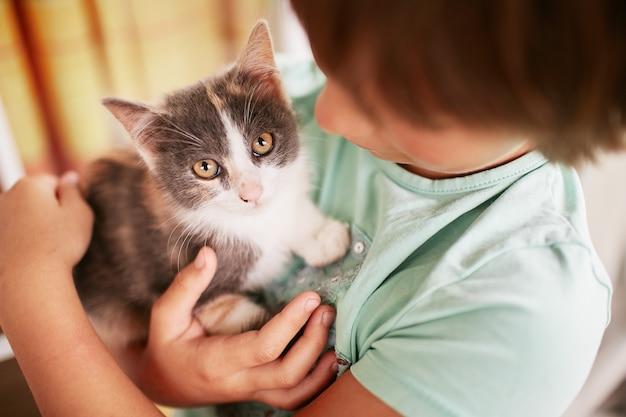 小さな男の子は彼の肩に黒と白の子猫を保持します。 無料写真