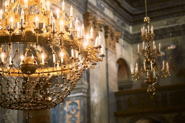 黄金のシャンデリアが教会の天井からハングします。 無料写真