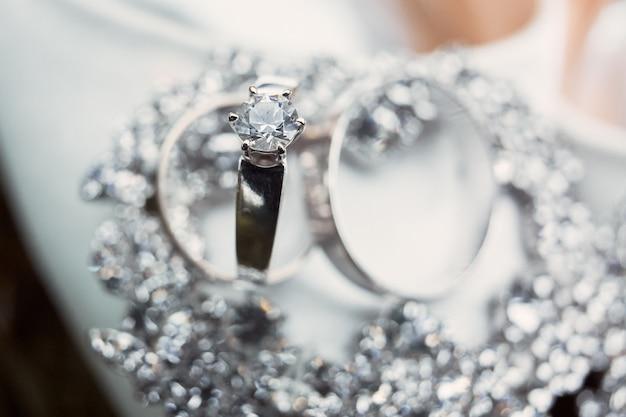 ホワイトゴールドで作られた上品なシルバーの結婚指輪はクリスタルブレスレットの上にあります 無料写真
