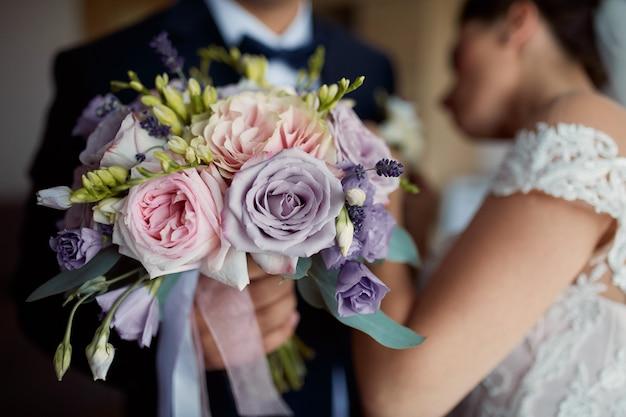 彼は結婚式のブーケを保持しながら新郎のジャケットに花嫁ピンブートニア 無料写真
