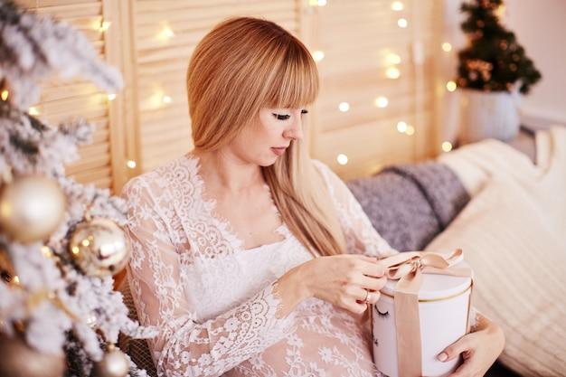 妊娠中の女性の肖像画、新年の雰囲気。魅力的な金髪の女性を期待して 無料写真