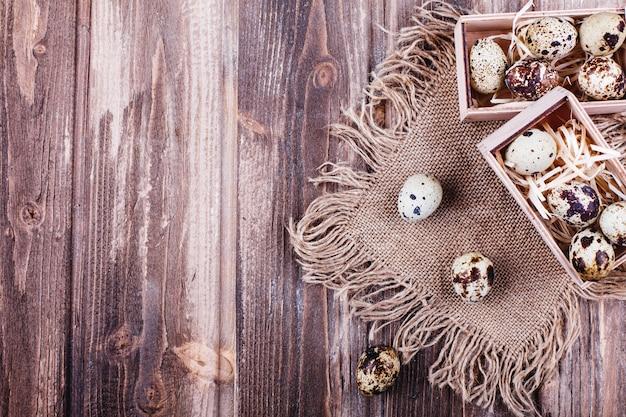 生鮮健康食品、タンパク質。木製の箱でウズラの卵は素朴なテーブルの上に立つ 無料写真
