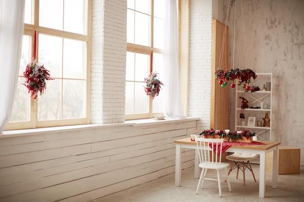 冬の休日の装飾。スタジオの準備赤い果実とクリスマスツリーの花輪 無料写真