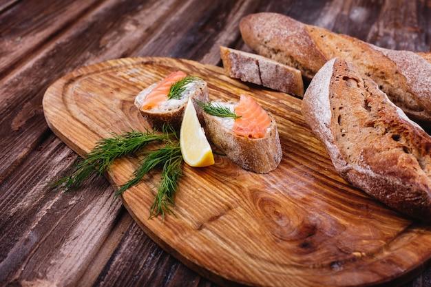 新鮮で健康的な食べ物。軽食や昼食のアイデア。レモンとサーモンの自家製パン 無料写真