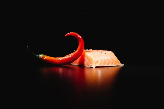 新鮮でおいしい、そして健康的な食事。分離された黒の背景に赤サーモンと唐辛子 無料写真