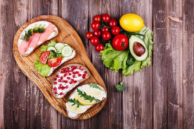 新鮮で健康的な食べ物。軽食や昼食のアイデア。自家製のパン、チーズ、アボカド 無料写真
