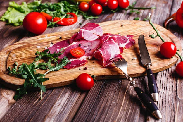 新鮮で健康的な食べ物。スライスした赤身の肉はルッコラと木製のテーブルの上にあります。 無料写真