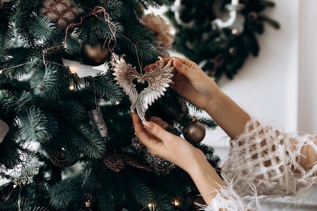 白いドレスを着た魅力的なブロンドの女性は大きなクリスマスツリーと部屋でポーズします。 無料写真