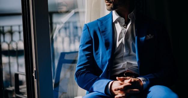 青いスーツを着た思慮深い人が窓辺に座っています。 無料写真