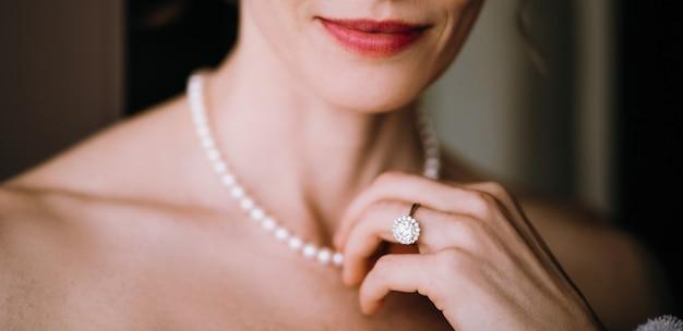 女性は彼女の首に柔らかい真珠のネックレスに触れる 無料写真