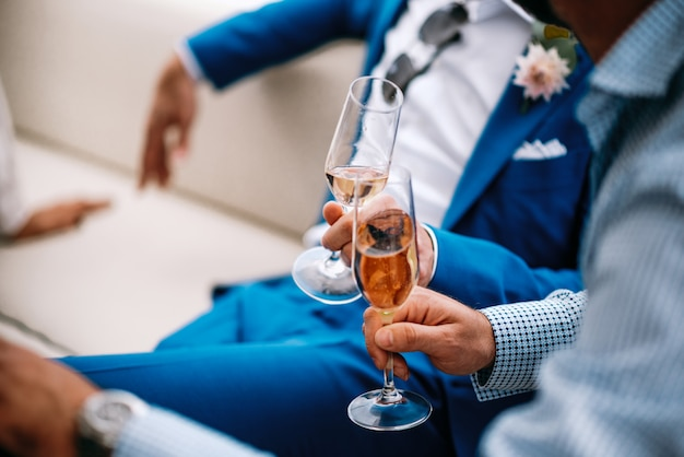 青いスーツを着た男性はソファに座って自分のメガネを張る 無料写真