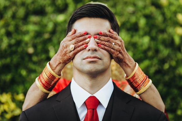 Традиционная индуистская свадьба. невеста обнимает нежного жениха сзади Бесплатные Фотографии
