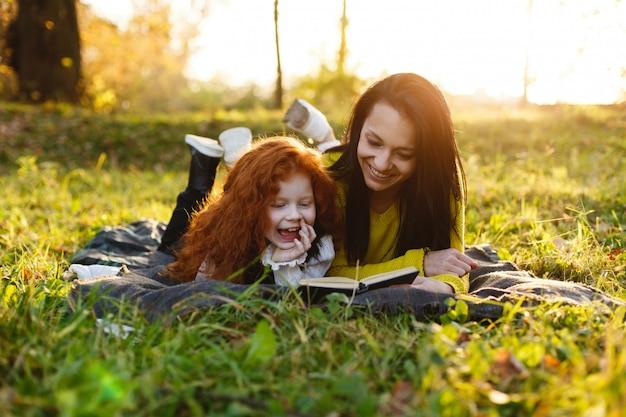 秋の雰囲気、家族の肖像画。魅力的なママと彼女の赤い髪の娘は、落ちた人の上に座って楽しんでいます 無料写真