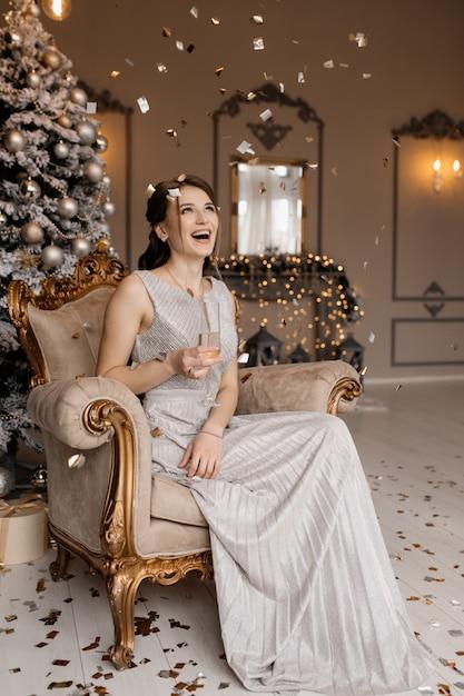 彼女の手にシャンパングラスとクリスマスツリーの前に銀のドレスでかわいい女が座っています。 無料写真