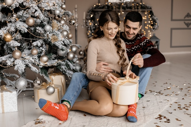 居心地の良い自宅の服で魅力的な若いカップルがクリスマスツリーの前にプレゼントボックスを開きます 無料写真