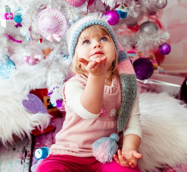 クリスマスツリーの近くに座っている美しい少女 無料写真