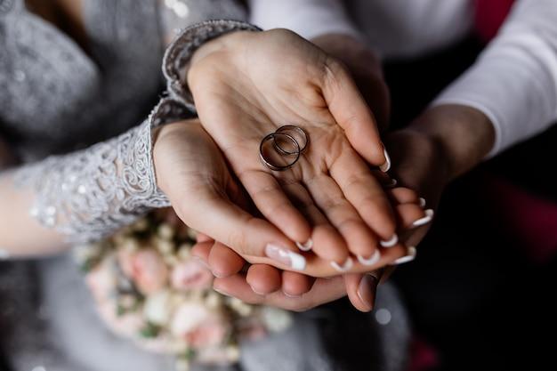 新婚夫婦は彼らの手で結婚指輪を握る 無料写真