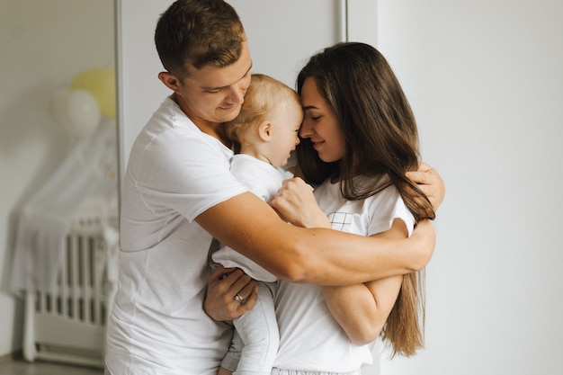 Отец крепко обнимает свою жену и маленького ребенка Бесплатные Фотографии