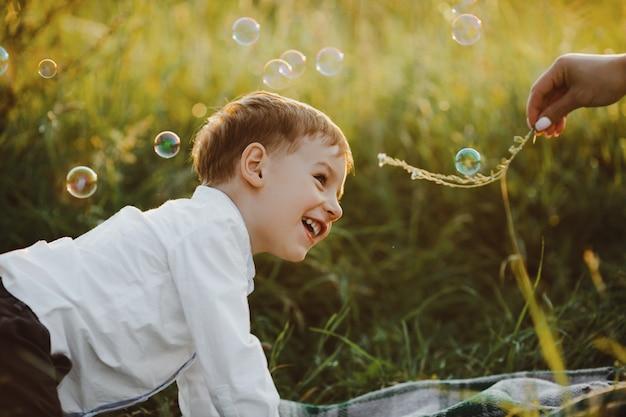 魅力的な小さな男の子は緑の芝生の上にあり、美しいを楽しんでいます 無料写真