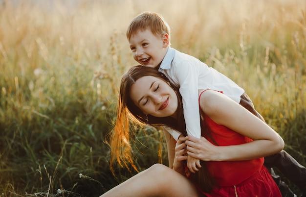 Семейный портрет, природа. очаровательная мама и сын играют на газоне б Бесплатные Фотографии