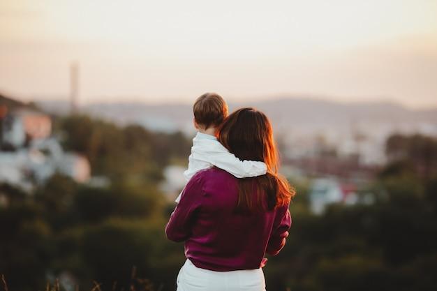 Очаровательная мама и сын играют на газоне Бесплатные Фотографии