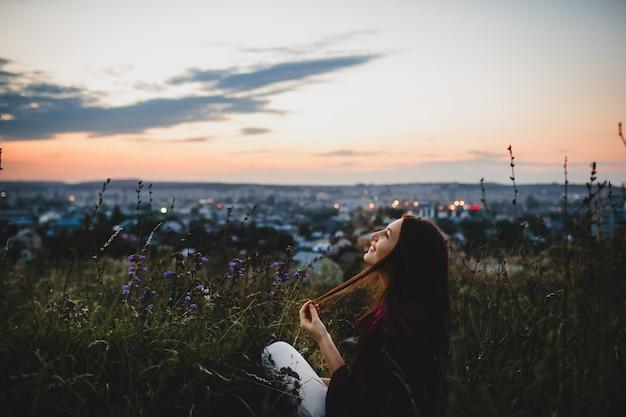 女性の肖像画、自然。紫のシャツを着た女性は草の上に座っています。 無料写真