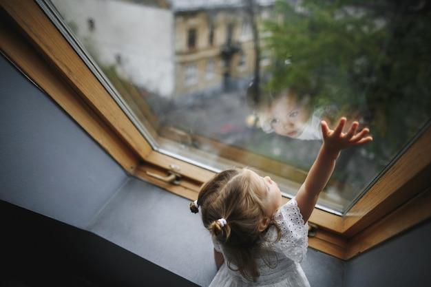 Маленькая девочка смотрит в окно Бесплатные Фотографии