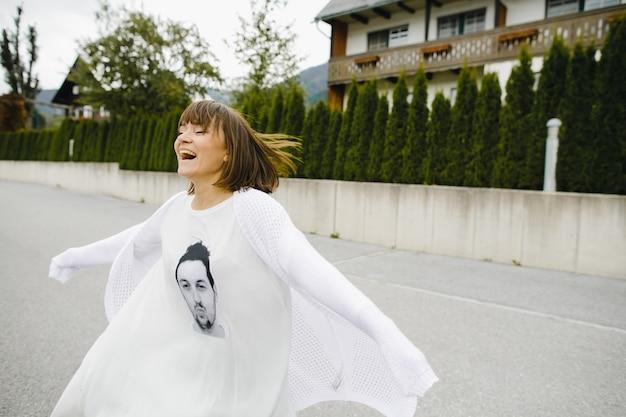 Улыбающаяся девушка бежит в белой одежде с мужским портретом Бесплатные Фотографии