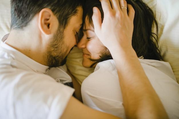 ベッドで抱いて喜んで夫と妻 無料写真