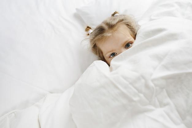 小さな女の子はベッドに隠れた 無料写真